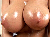 Milf playing with her oiled monster breasts.